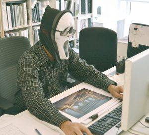 photo of person wearing scream mask at a computer
