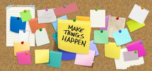 "Bulletin board with colorful post-it notes and message ""make things happen."""