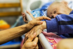 Photo of someone holding hand of elderly patient in bed